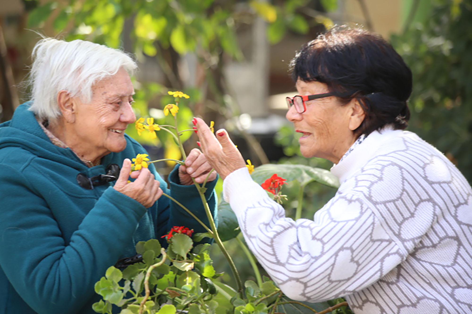 dos mujeres adultas mayores mirando flores