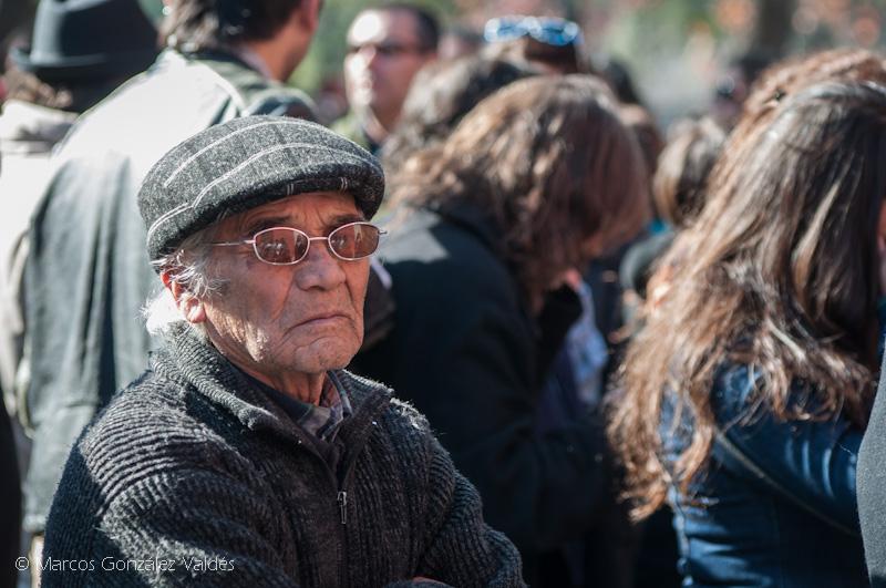 hombre adulto mayor sentado entre el público