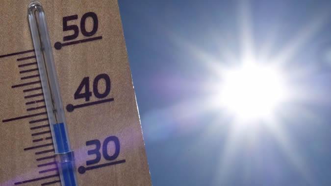 Foto del sol y termómetro midiendo la temperatura