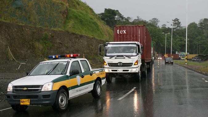 Foto de una carretera con camiones y policías