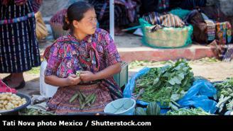 Mujer vendiendo en mercado de verduras