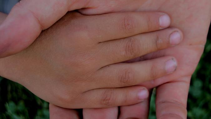 Adulto sosteniendo la mano de un niño